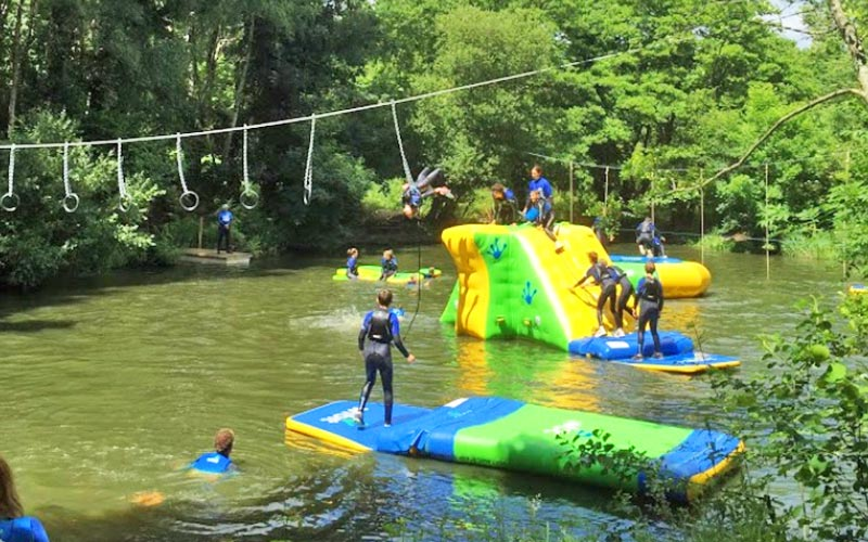 People climbing and stood on inflatable objects above water
