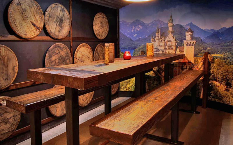 A tall wooden bench in Frankenstein Bierkeller, with a print of a castle on the wall behind it