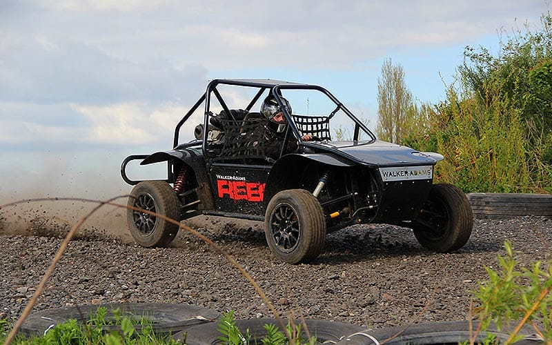 A rally buggy racing around a track lined by tyres