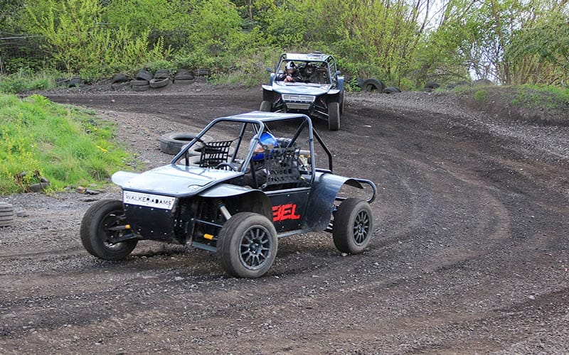 Two rally buggies racing around an outdoor track with greenery in the background and tyres surrounding the track