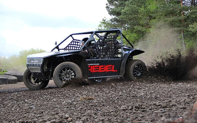 A rally buggy kicking up gravel as it drives