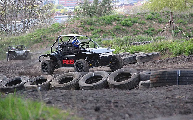 Two rally buggies driving around an outdoor track, with several tyres lining the tracks
