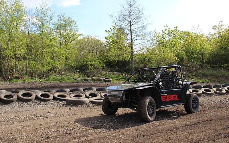 A rally buggy driving along a track with tyres lining the outskirts
