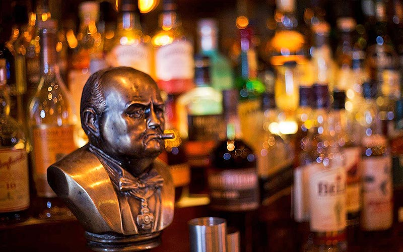 A bust on a bar, with blurred spirit bottles in the back
