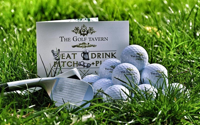 The Golf Tavern menu in grass, next to a golf club and golf balls