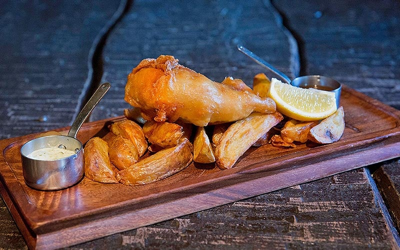 Fish and chips served on a wooden board