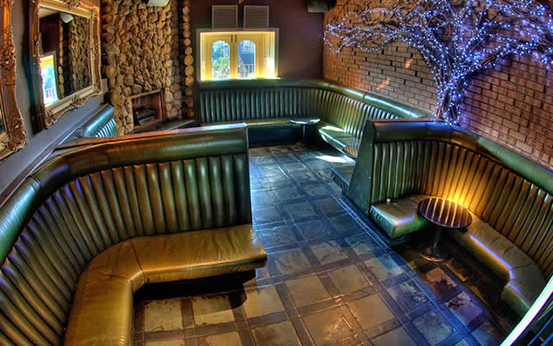 Leather booths against exposed brick walls in Espionage