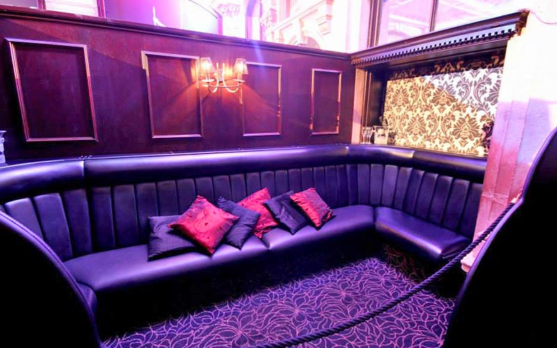 A booth with leather seats and wooden panels within the strip club