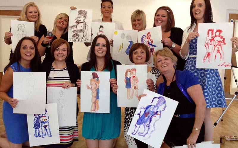 A group of women holding up their drawings during a nude life drawing class