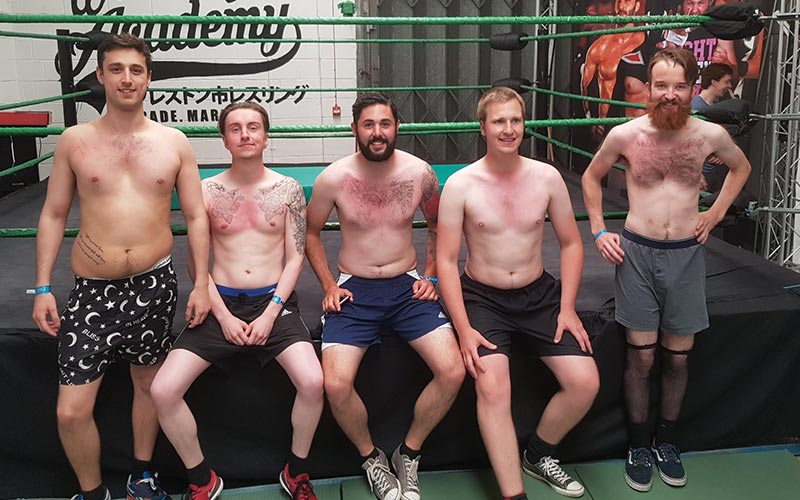 Five men in shorts, posing for a picture in front of a wrestling ring