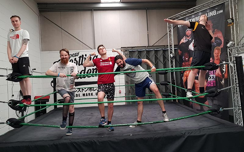 Five men posing for a picture in front of a wrestling ring