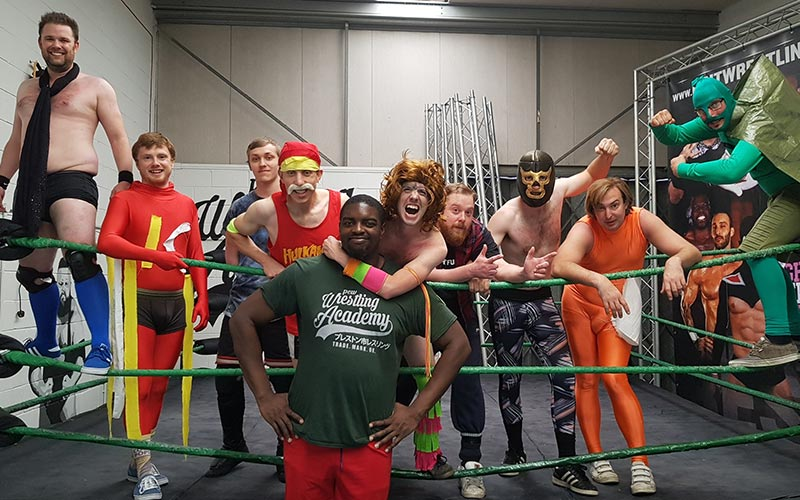 Some men in a wrestling ring, all dressed up in fancy dress