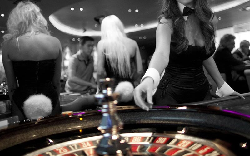 A black and white image of a girl dressed sexily, playing Roulette
