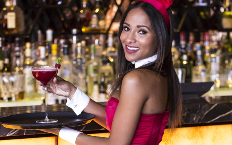 A girl holding a glass of wine at the bar, dressed as a bunny girl