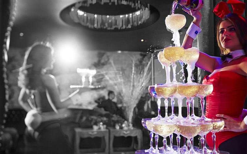 A Champagne tower being poured by a bunny girl