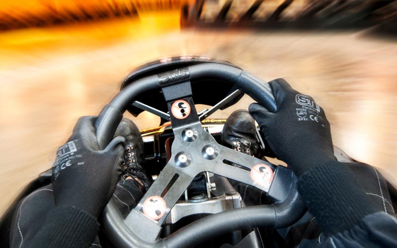 A pair of hands on a steering wheel of a go kart