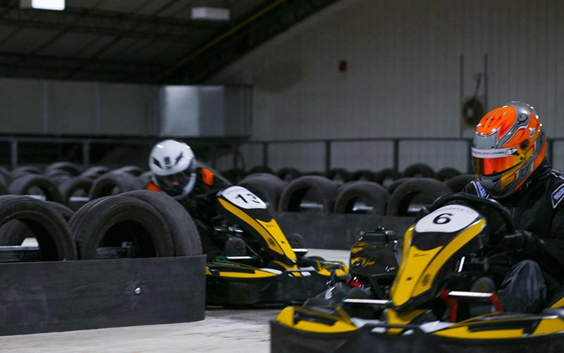 Two people wearing overalls and helmets driving around an indoor track in go karts