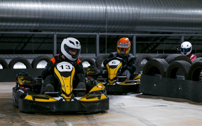Three people driving around an indoor track in go karts