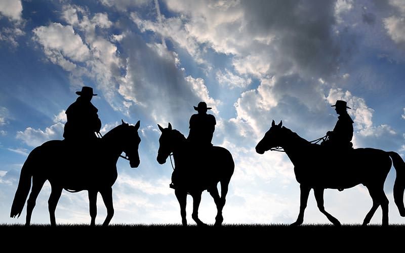 Black silhouettes of three people on horseback to a backdrop to a cloudy sky