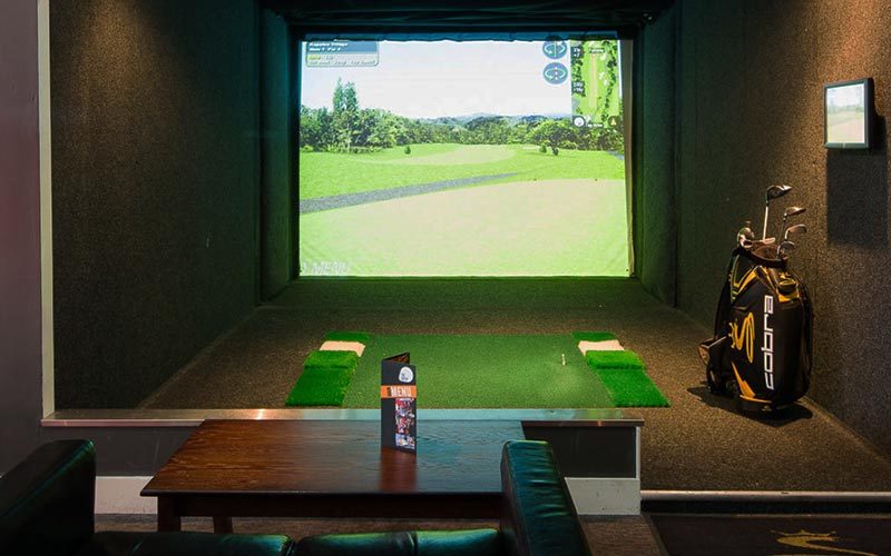 The screen of the golf simulator with some clubs in a bag to the side