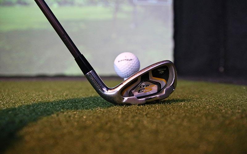 A golf club addressing a golf ball on a tee