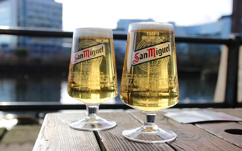 Two pints of San Miguel outside on a wooden table