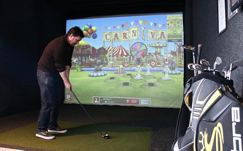 A man using the virtual golf simulator