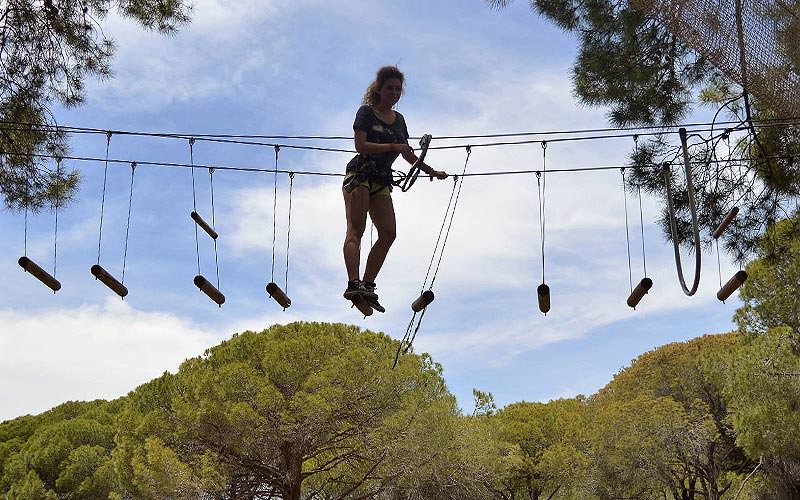 A woman walking on a rope ladder to a backdrop of trees