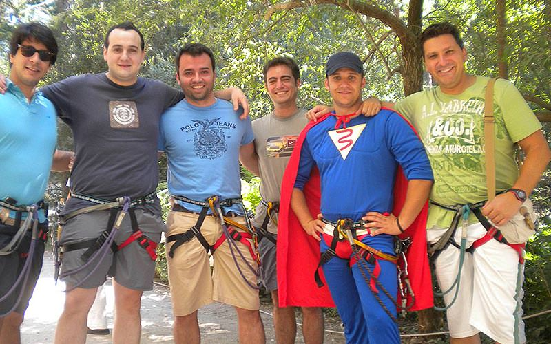 Five men posing in harnesses with a man in a superhero costume