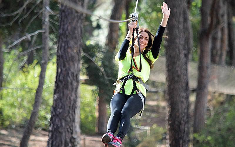 A woman swinging onto a zipline