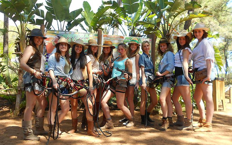 A group of women posing in cowboy style outfits whilst wearing harnesses