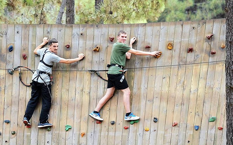 Two people posing whilst stood on a rock climbing wall