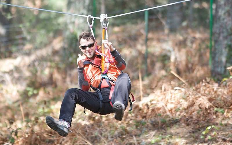 A man swinging on a zipline to a backdrop of the forest