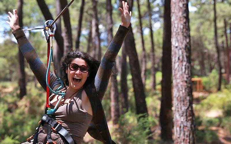 A close up of a woman swinging on a zipline