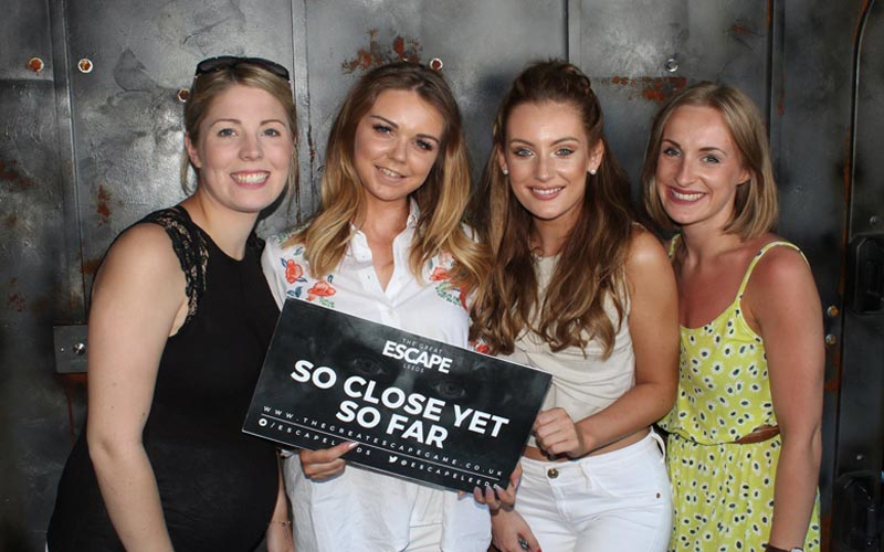 Four girls holding a 'so close yet so far' sign