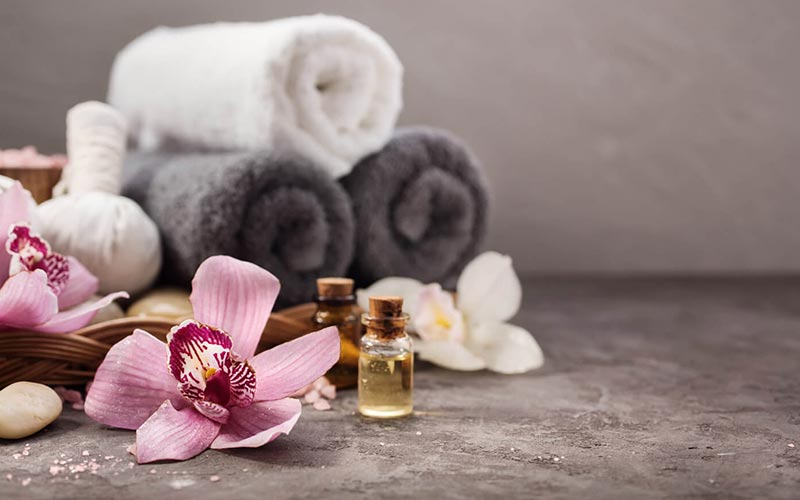 Massage oils and flowers, placed in front of rolled up towels