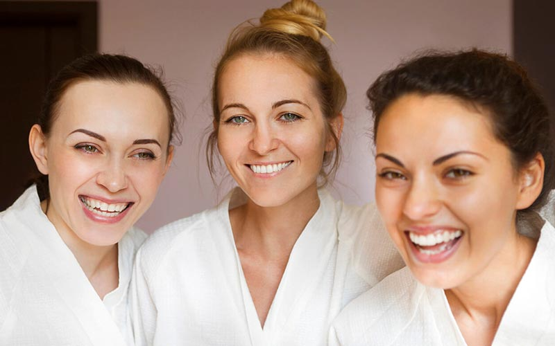Three women smiling whilst wearing white bathrobes