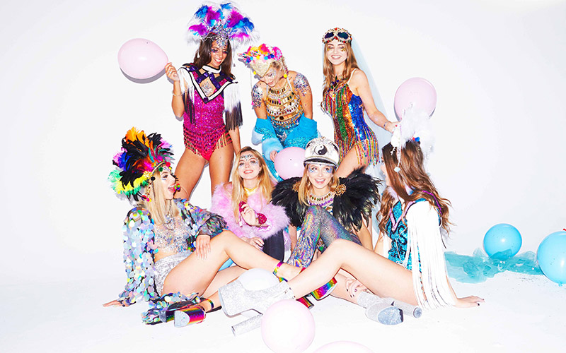 Seven girls dressed in fun, bright festival outfits, including feathers and balloons