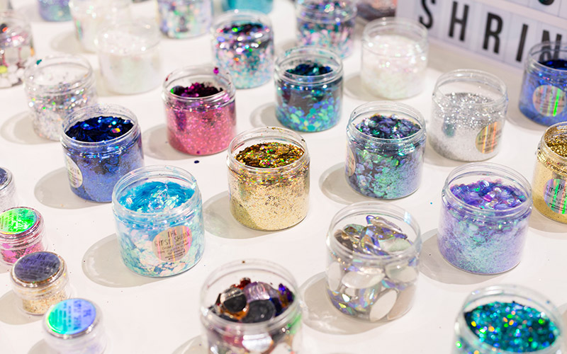 Lots of pots of glitter lined up in a uniform way on a white table