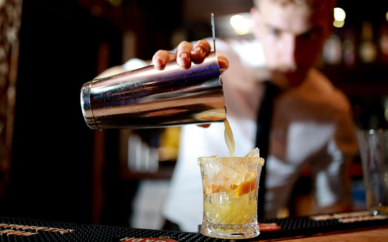 An orange cocktail being poured by a barman