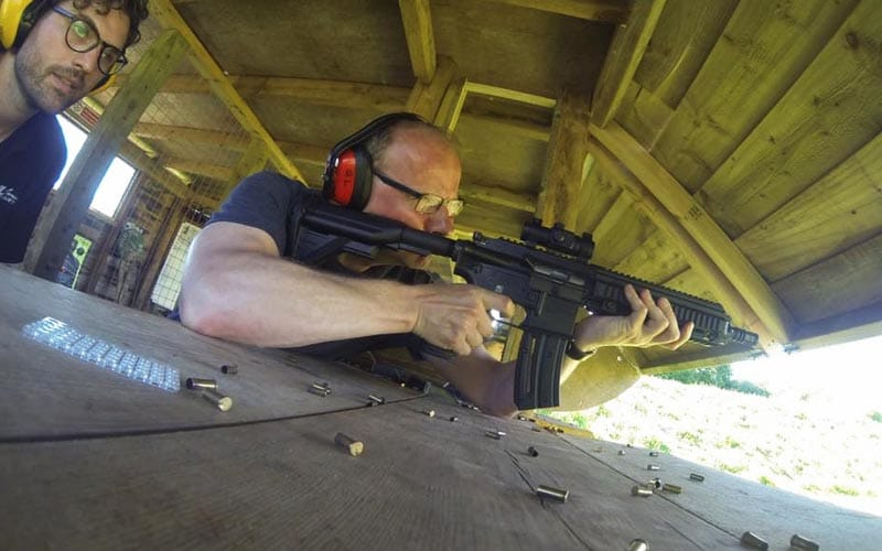 A man in a shooting range aiming a black assault rifle