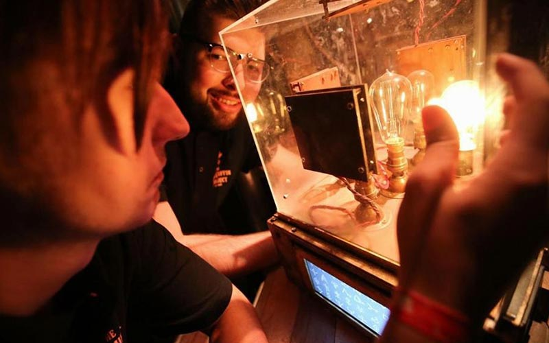 Two people looking into a glass box with lights inside