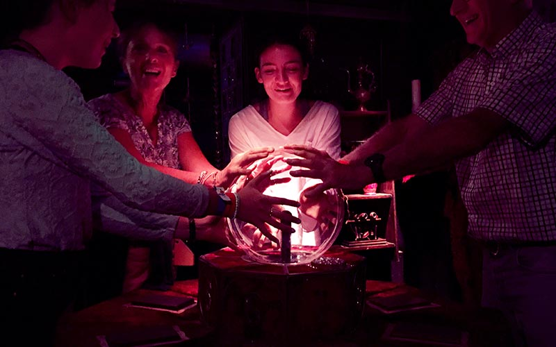 Four people with their hands on an electricity ball