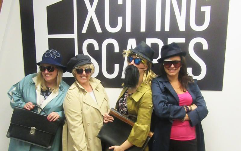 Image of four women dressed up with sunglasses and hats holding briefcases and standing infront of exciting escapes sign
