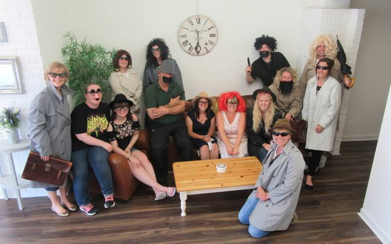 Image of a group of people sitting on a sofa and around in a room wearing sunglasses and hats and wigs and macs holding briefcases