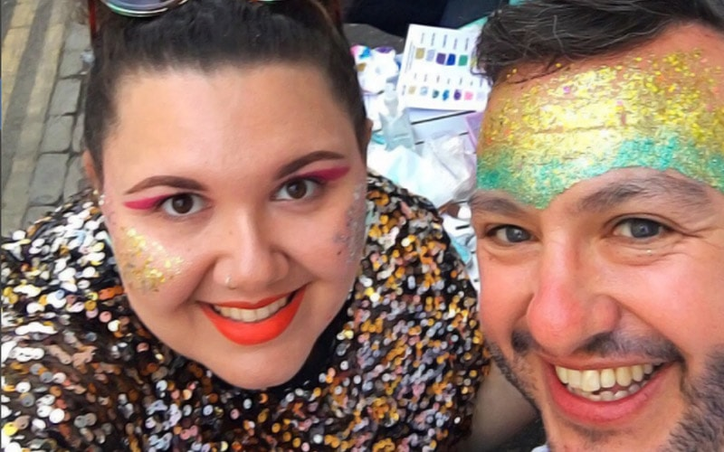 A man and a woman with rainbow glitter make up on