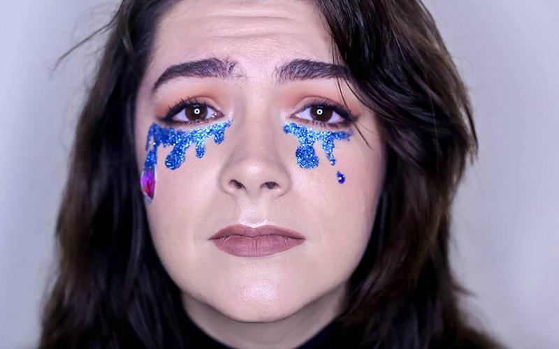 A woman with pink and blue tears drawn on in glittery make up