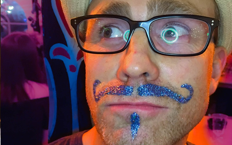 A man with a blue glittery goatee drawn on
