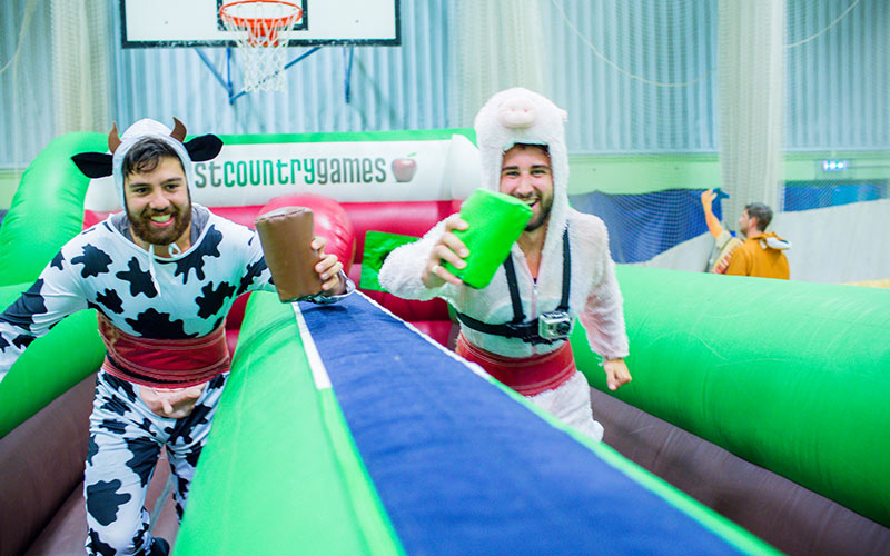Two men on the bungee run, dressed in fancy dress costumes