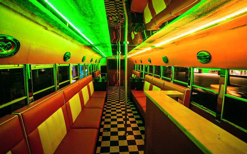 An inside of a school bus with neon lights